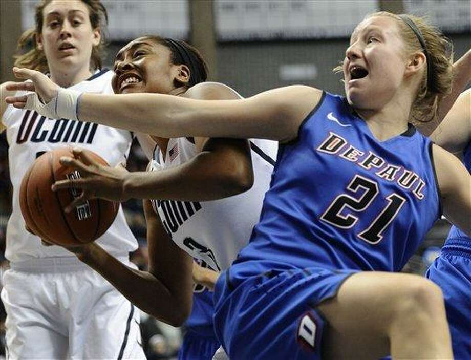 DePaul's Megan Rogowski, right, fouls Connecticut's Morgan Tuck, left, during the second half of an NCAA college basketball game in Storrs, Conn., Sunday, Feb. 10, 2013. Rogowski was top scorer for DePaul with 12 points.  Connecticut won 91-44. (AP Photo/Jessica Hill) Photo: AP / FR125654 AP