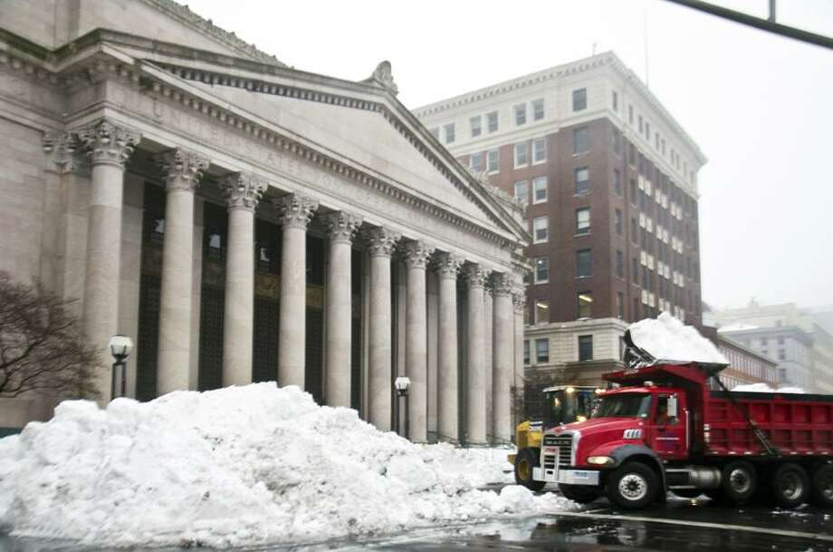 A payloader dumps snow into a truck for removal on Church Street across from the New Haven Green. Scenes like this can be found all over southern Conencticut, which has kept area girls basketball teams from seeing the court since Friday.     Melanie Stengel/Register