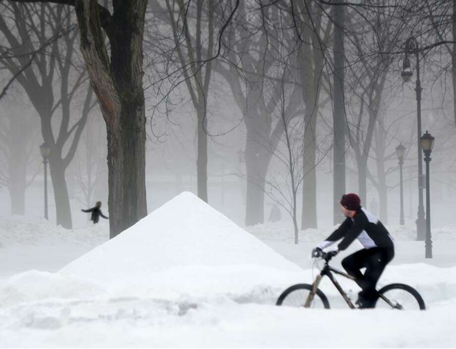 Bicyclists and pedestrians make their way across the New Haven Green, where someone has built a pyramid snow sculpture. With most schools not in session Monday and Tuesday, many athletic events have also been postponed.   Melanie Stengel/Register.