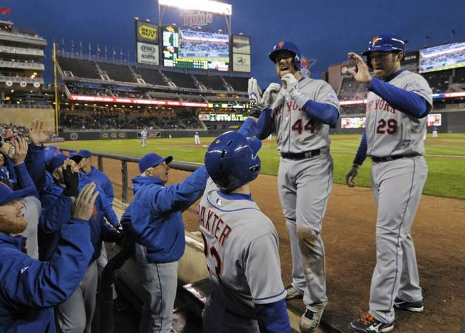 New York Mets' John Buck (44) is welcomed at the dugout after his grand slam off Minnesota Twins pitcher Pedro Hernandez in the second inning of a baseball game on Friday, April 12, 2013, in Minneapolis.  Mets' Ike Davis, right, looks on. (AP Photo/Jim Mone) Photo: AP / AP2013