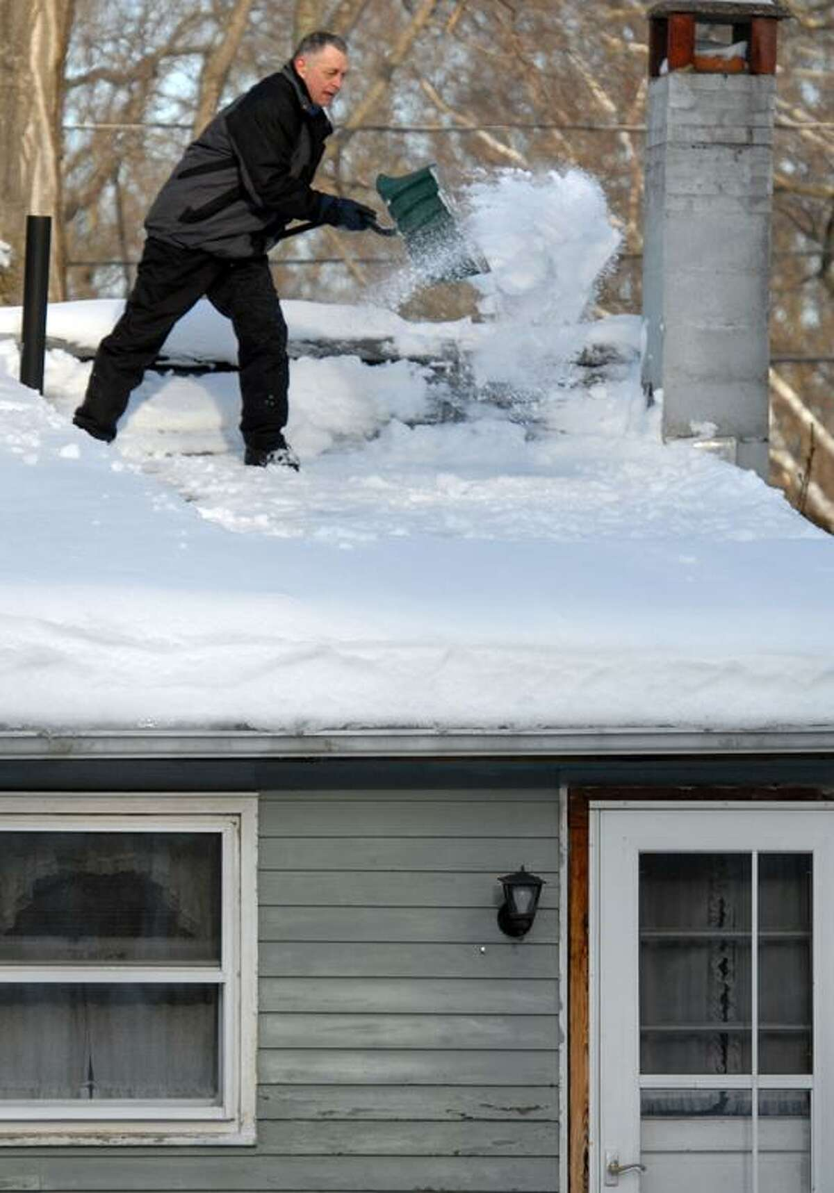 The Blizzard of 2013, Nemo. Bill Mauzey of Ivoryton (Essex) clears the snow off his roof. Mara Lavitt/New Haven Register2/10/13
