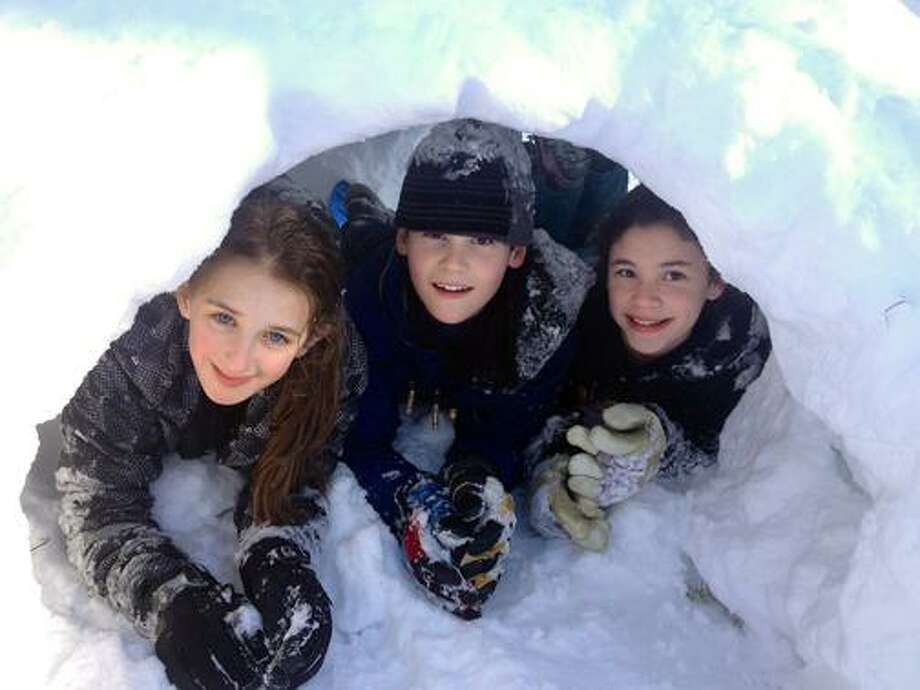 Submitted by Tina Cienava Clemmey   My twelve year old twins, Ben and Abbey Clemmey and our neighbor Maeve Williams, at left peek out of the entrance of the igloo they are making in our backyard on Old Mill Road in Middletown.