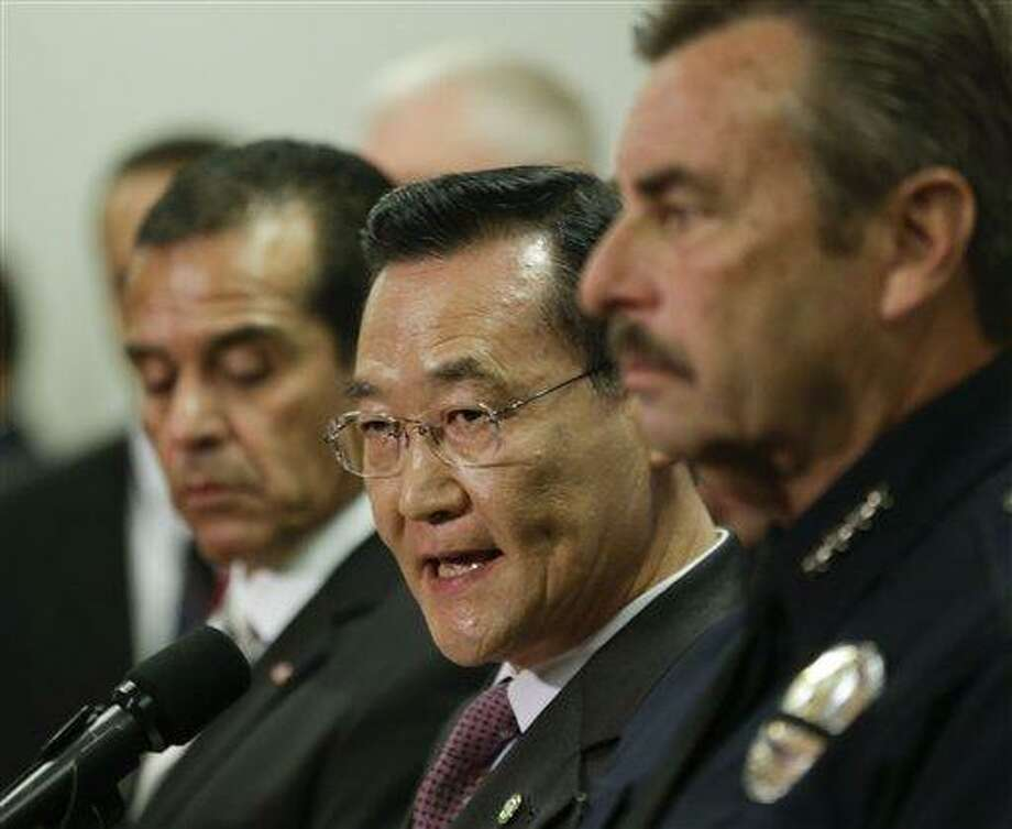 Irvine, Calif., Mayor Steven Choi, center, talks about the $1,000,000 reward for accused killer and fired Los Angeles police officer, Christopher Dorner as Los Angeles Mayor, Antonio Villaraigosa, left, and Los Angeles Police Chief Charlie Beck look on during a new conference at the Los Angeles police department in Los Angeles, Sunday, Feb. 10, 2013.  (AP Photo/Chris Carlson) Photo: AP / AP