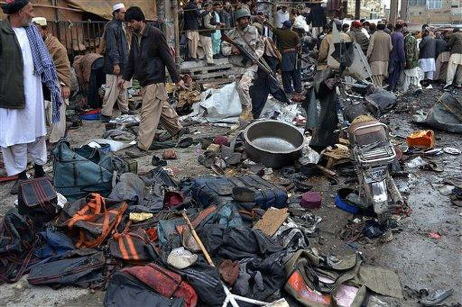 A Pakistani paramilitary soldier and local residents gather at the site of bomb blast in Quetta, Pakistan, Thursday, Jan. 10, 2013. A bomb targeting paramilitary soldiers killed scores of people in southwest Pakistan, officials said. (AP Photo/Arshad Butt) Photo: AP / AP