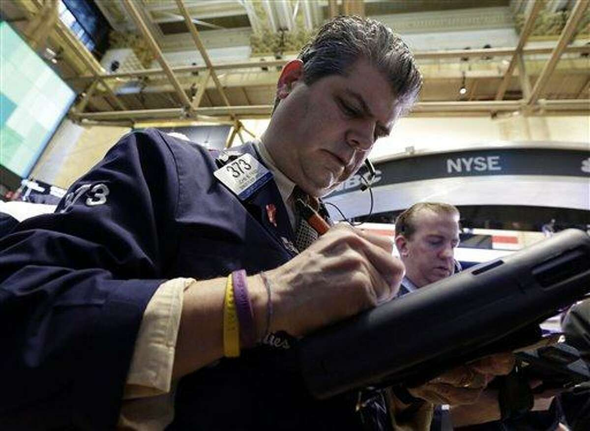 Trader John Panin, left, works on the floor of the New York Stock Exchange Wednesday, March 13, 2013. Investors are calling an end to the past week's remarkable rally, with many cashing in on stocks Wednesday despite more strong economic data out of the U.S. (AP Photo/Richard Drew)