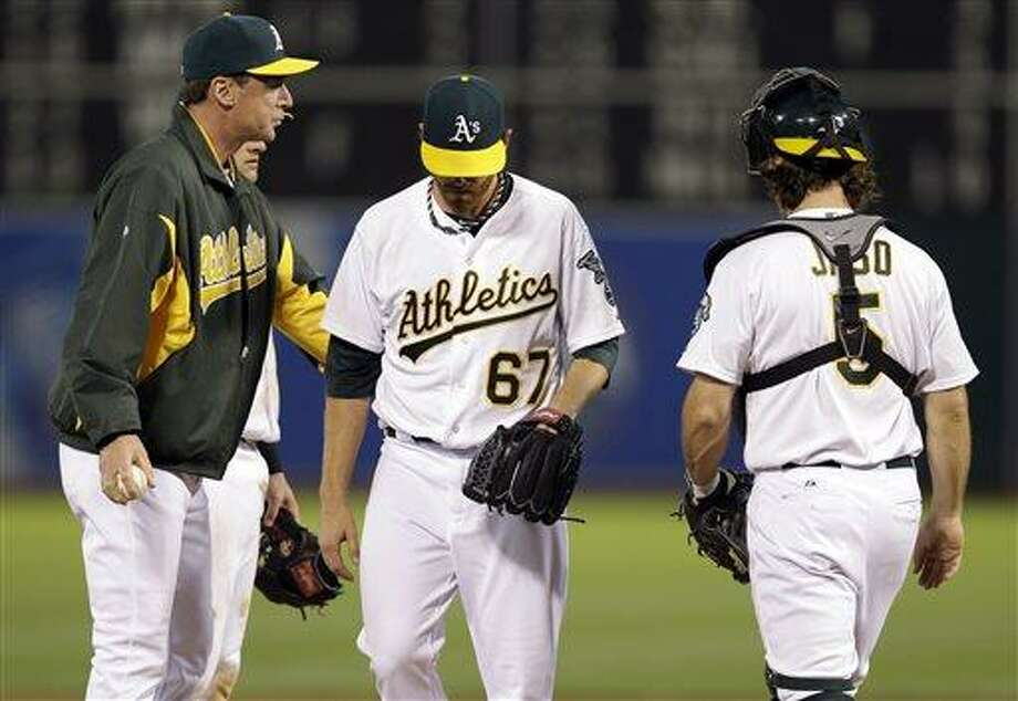 Oakland Athletics starting pitcher Dan Straily (67) is pulled from the game by manager Bob Melvin, left, during the fifth inning of a baseball game against the Los Angeles Angels on Monday, April 29, 2013 in Oakland. Calif. (AP Photo/Marcio Jose Sanchez) Photo: AP / AP