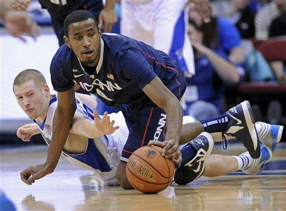 Connecticut's Deandre Daniels, right, beats Seton Hall's Kyle Smyth to a loose ball during the first half of an NCAA college basketball game on Sunday, Feb. 10, 2013, in Newark, N.J. (AP Photo/Bill Kostroun) Photo: AP / FR51951 AP