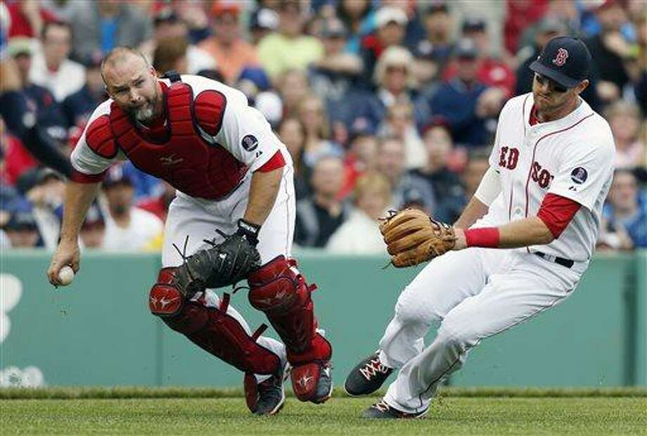 Boston Red Sox's David Ross, left, fields the ball next to teammate Will Middlebrooks on a sacrifice bunt by Toronto Blue Jays' Munenori Kawasaki in the third inning of a baseball game in Boston, Saturday, May 11, 2013. Kawasaki was out at first. (AP Photo/Michael Dwyer) Photo: AP / AP