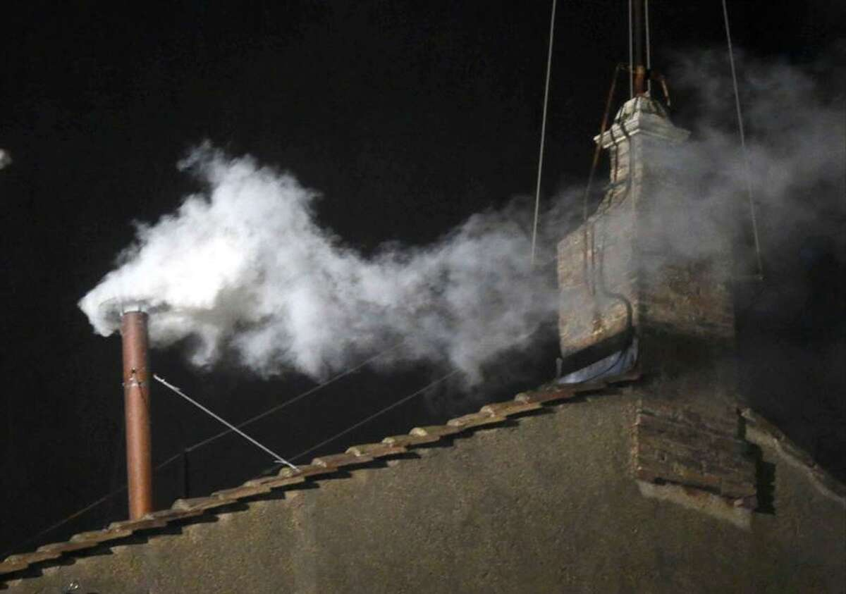 White smoke emerges from the chimney on the roof of the Sistine Chapel, in St. Peter's Square at the Vatican, Wednesday, March 13, 2013. The white smoke indicates that the new pope has been elected. (AP Photo/Gregorio Borgia)