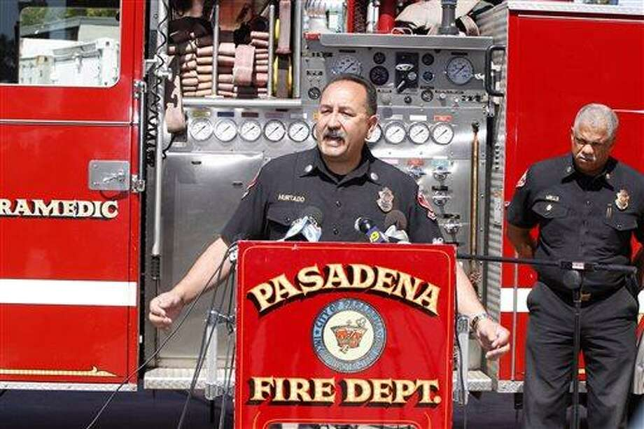Art Hurtado, Pasadena Fire captain and paramedic takes questions during a news conference in Pasadena, Calif., Thursday, April 11, 2013. At right, Calvin Wells Pasadena Fire Chief. Hurtado helped save the life of a man at Home Depot after the victim apparently tried to cut his arms off using handsaws found at the home improvement store in West Covina, Calif. (AP Photo/Damian Dovarganes) Photo: AP / AP