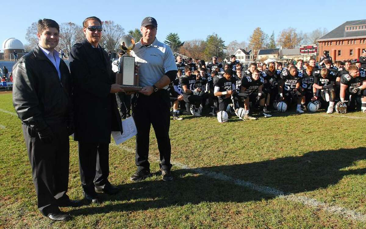 Catherine Avalone/The Middletown Press Mayor Dan Drew and Middletown Hall of Fame President Tom Serra present the city championship trophy to Xavier football coach Sean Marinan in 2012. Xavier won the final game with Middletown on Thanksgiving, 41-14.