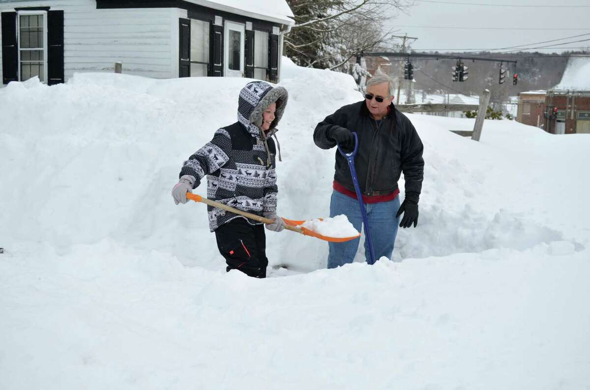 Ray Binette gets some help shoveling from his granddaughter Lexi Walsh on Saturday at his home on Pearl St in Torrington.John Berry/Register Citizen.