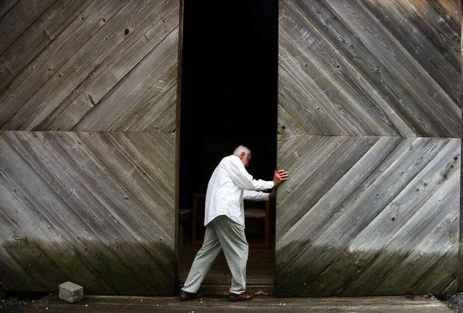 REDDING- Father John Guiliani, owner of Benedictine Grange Cemetary, slides open the doors to the barn where the funeral ceremony was conducted for convict Micheal Bruce Ross eight years ago. For ten years Guiliani was Ross's spiritual advisor before Ross was sentenced to death through lethal injection by the state of Connecticut after killing eight young women in eastern Connecticut.                 Chynna Davis/For the Register / Chynna Davis