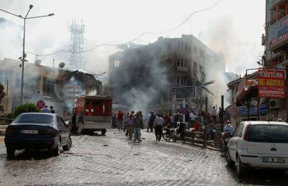 Firefighters work at one explosion site after several explosions killed at least 18 people and injured dozens in Reyhanli, near Turkey's border with Syria, Saturday, May 11, 2013, Turkish Interior Minister Muammer Guler said Photo: ASSOCIATED PRESS / AP2013