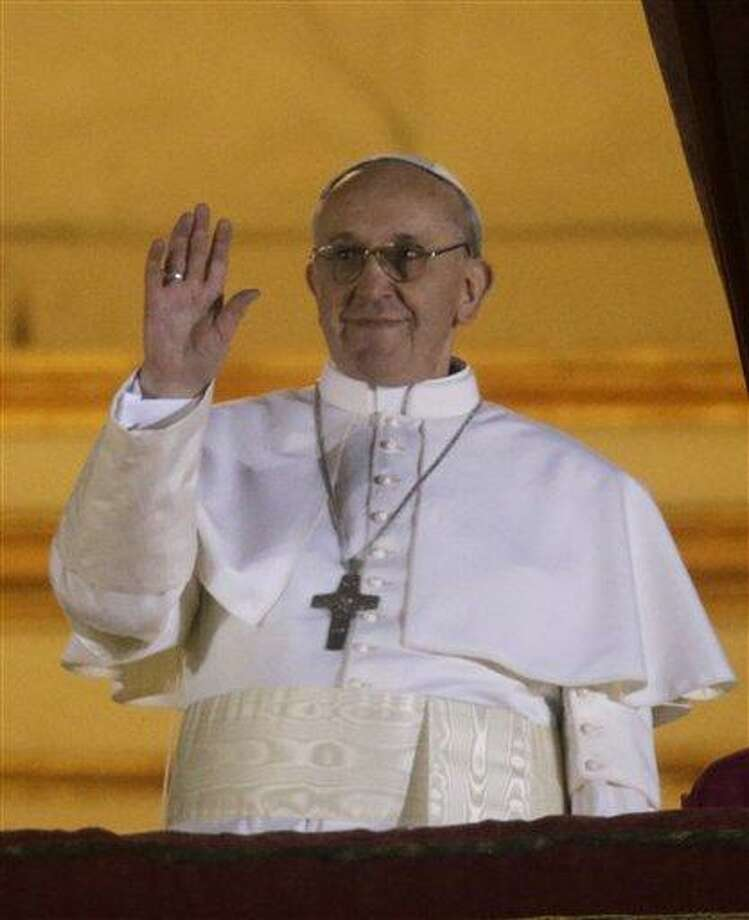 Pope Francis waves to the crowd from the central balcony of St. Peter's Basilica at the Vatican, Wednesday, March 13, 2013. Cardinal Jorge Bergoglio who chose the name of  Francis is the 266th pontiff of the Roman Catholic Church. (AP Photo/Gregorio Borgia) Photo: AP / AP