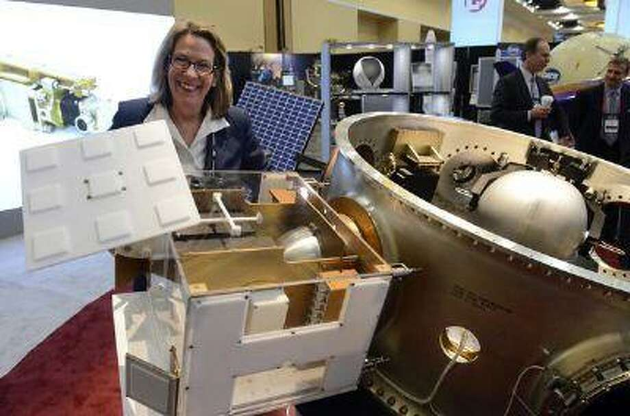 COLORADO SPRINGS, CO. - APRIL 9TH: PlanetiQ President and CEO, Anne Hale Miglarese, stands next to an actual scale model of a weather satellite attached to a MOOG payload adapter on display inside the Lockheed Martin Exhibit Center for the 29th National Space Symposium at the Broadmoor Hotel in Colorado Springs, Tuesday morning, April 9th, 2013. PlanetiQ collects critical environmental data from the satellites. The MOOG Paylaod adapter allows for six secondary satellites to share a ride on a Delta IV or Atlas V Lauch vehicle with a large primary satellite. (Photo By Andy Cross/The Denver Post) Photo: DP / Copyright - 2013 The Denver Post, MediaNews Group.