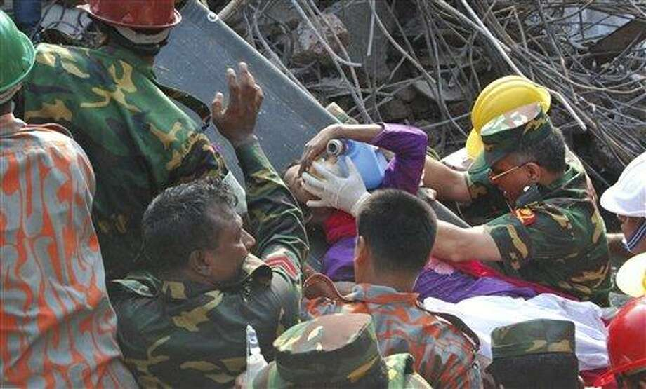 Rescuers carry a survivor pulled out from the rubble of a building that collapsed in Saver, near Dhaka, Bangladesh, Friday, May 10, 2013. Rescue workers in Bangladesh freed the woman buried for 17 days inside the wreckage of a garment factory building that collapsed, killing more than 1,000 people. Soldiers at the site said her name was Reshma and described her as being in remarkably good shape despite her ordeal. (AP Photo/Parvez Ahmad Rony) Photo: AP / AP
