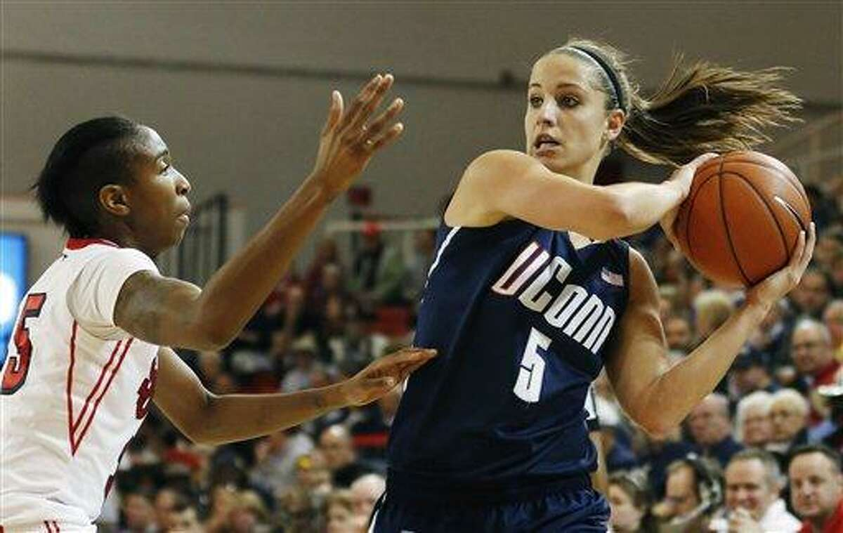 Connecticut guard Caroline Doty (5) looks to pass around St. John's guard Shenneika Smith (35) during the first half of an NCAA college basketball game, Saturday, Feb. 2, 2013, at St. John's University in New York. (AP Photo/John Minchillo)
