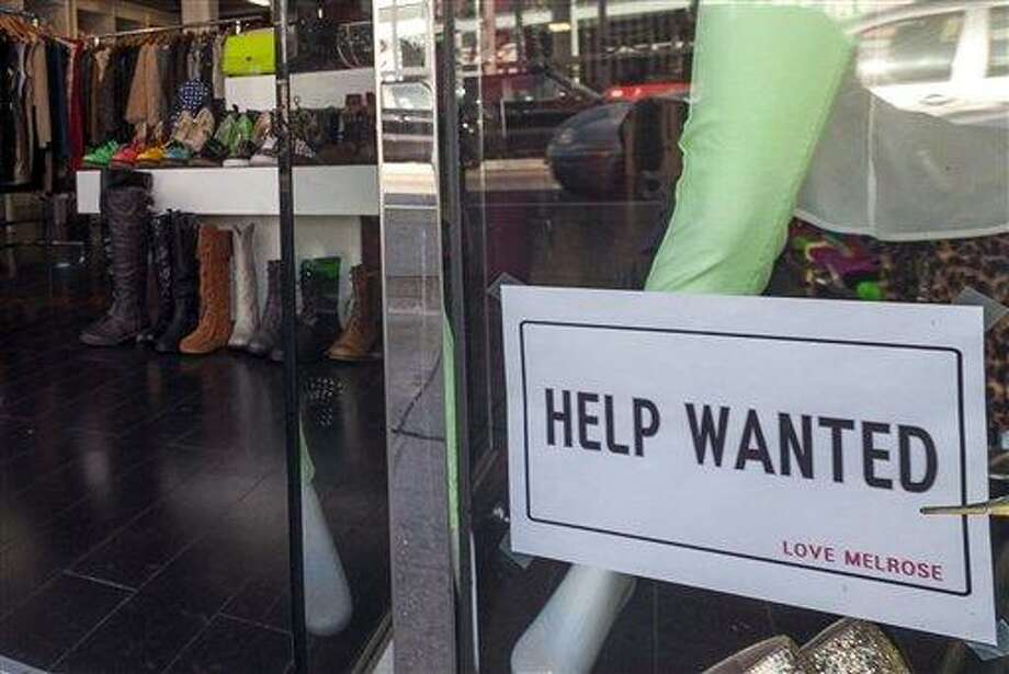 In this  Friday, Dec. 7, 2012, photo, a help wanted sign is posted on the front window of a clothing boutique in Los Angeles.The number of Americans seeking unemployment benefits fell sharply for a fourth straight week, a sign that the job market may be improving. The Labor Department said Thursday, Dec. 13, 2012, that weekly applications for unemployment benefits fell 29,000 last week to a seasonally adjusted 343,000, the lowest in two months. It is the second-lowest total this year.  (AP Photo/Damian Dovarganes) Photo: ASSOCIATED PRESS / The Associated Press2012