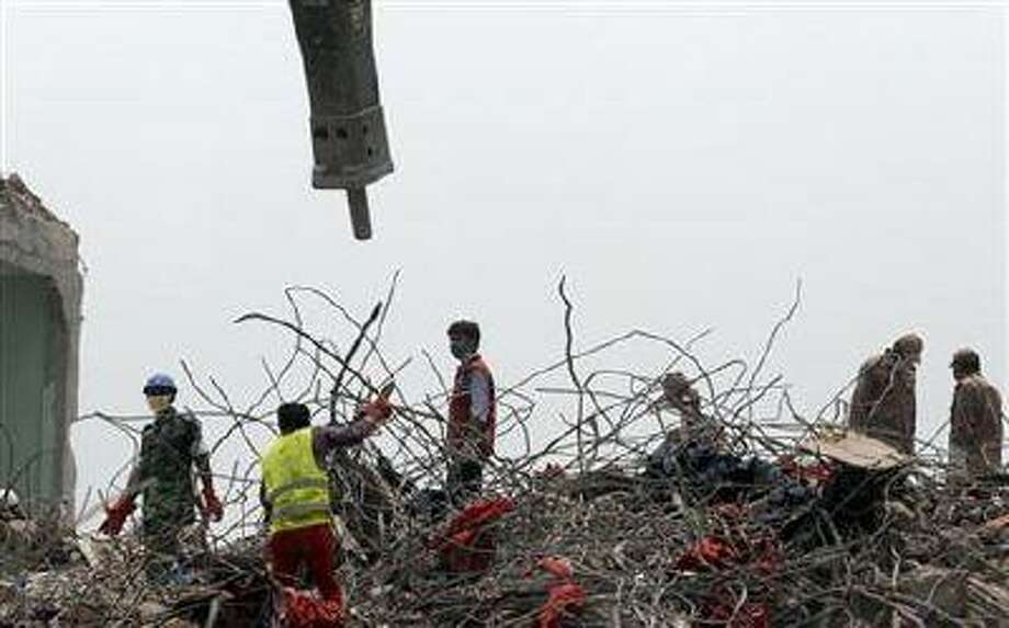 Rescuers work at the site of the eight-story Rana Plaza building that collapsed in Savar, near Dhaka, Thursday, May 9, 2013.