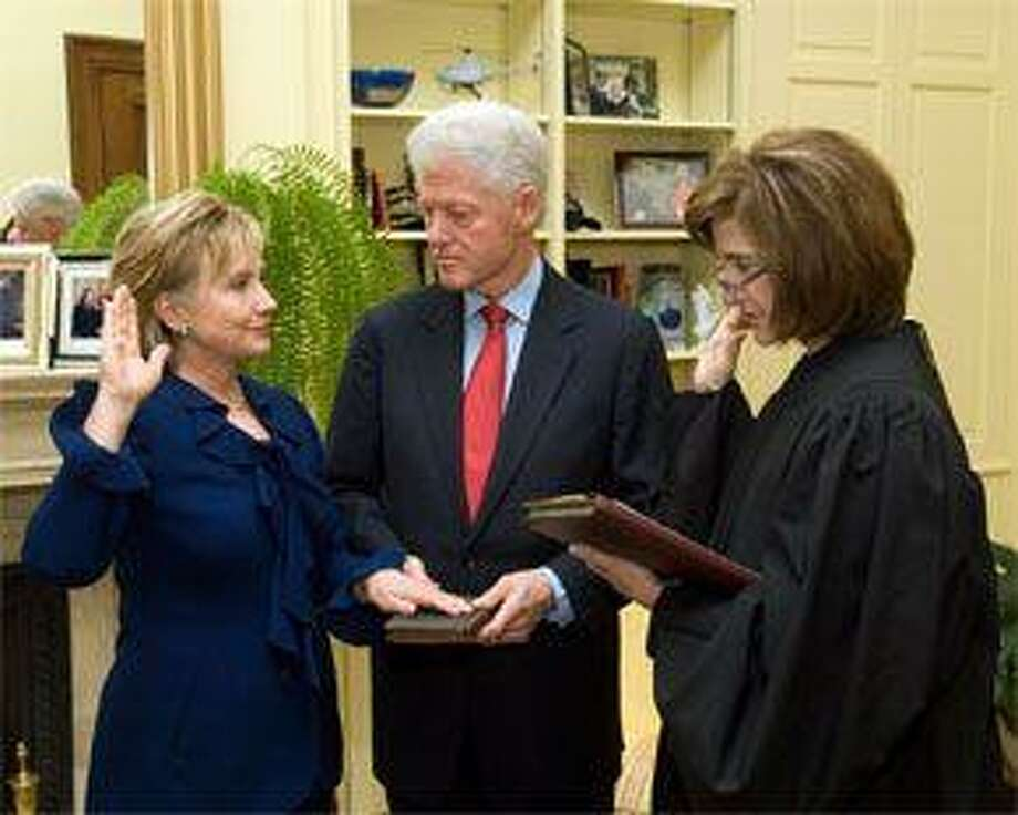 Hillary Rodham Clinton takes the oath of office as Secretary of State, administered by Associate Judge Kathryn Oberly, as Bill Clinton holds the Bible.