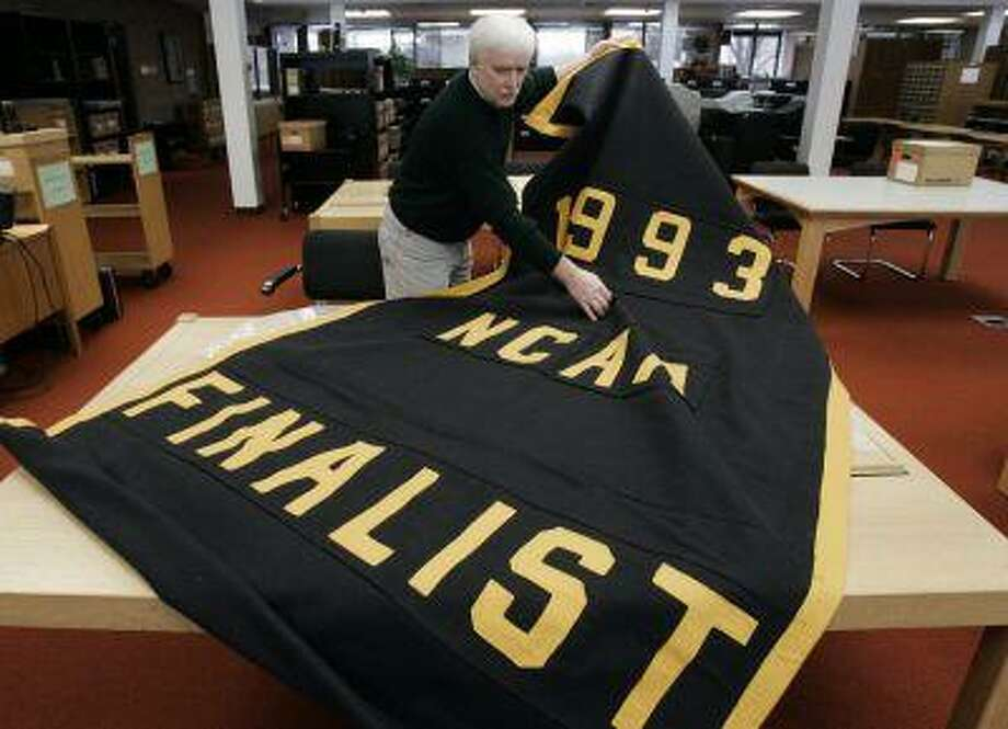 In this Feb. 6, 2007, file photo, Greg Kinney, archivist at the University of Michigan Bentley Historical Library, unrolls the 1993 NCAA basketball tournament finalist banner being kept in storage in Ann Arbor, Mich. The banner was taken down from the university's Crisler Arena as part of self imposed sanctions following what the NCAA said was the largest financial scandal, and one of the worst of any kind, in the history of college athletics. Michigan's 10-year dissociation from Chris Webber, Maurice Taylor and Louis Bullock ended on May 8, 2013. The former Wolverines can formally reconnect with the school after one of the biggest scandals in NCAA history. (AP Photo/Paul Sancya) Photo: AP / AP