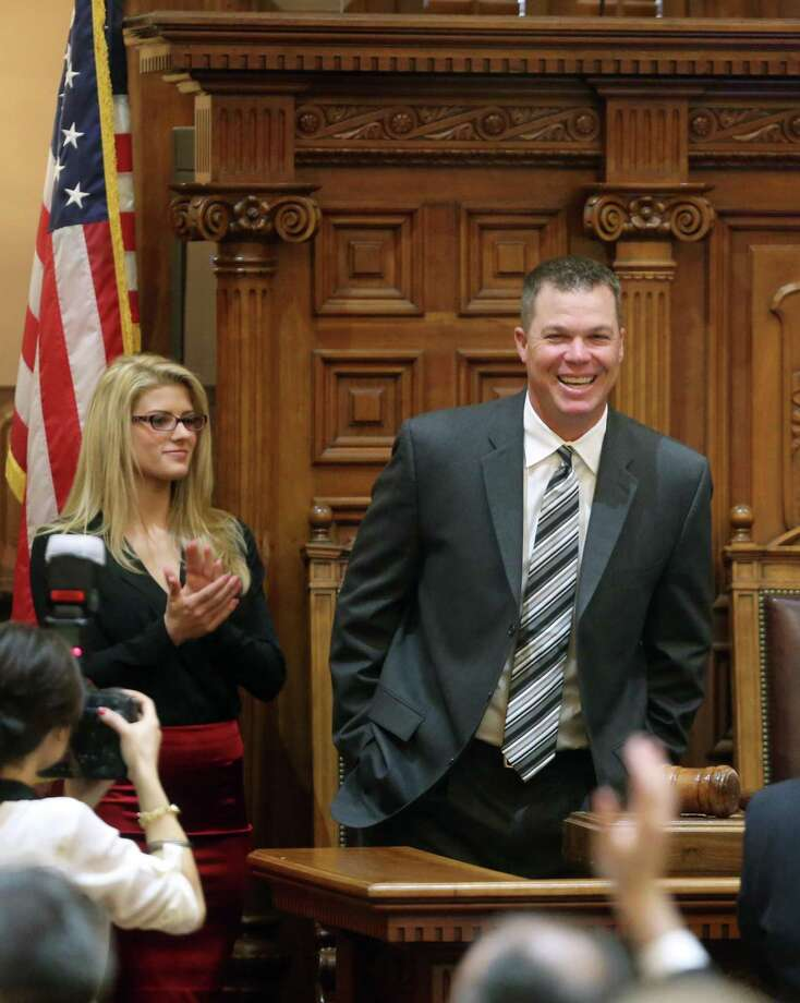 Former Atlanta Brave baseball player Chipper Jones, right, reacts as he stands next to his girlfriend Taylor Higgins where he was honored in the House Chambers at the Capitol, Tuesday, March 5, 2013, in Atlanta. The retired third baseman came to the Capitol Tuesday to collect resolutions and accolades from legislators and others.   (AP Photo/Atlanta Journal-Constitution, Jason Getz) Photo: ASSOCIATED PRESS / 2013 Atlanta Journal Constitution  - No Mags, no sales, internet out, editorial use only. Marietta D2013
