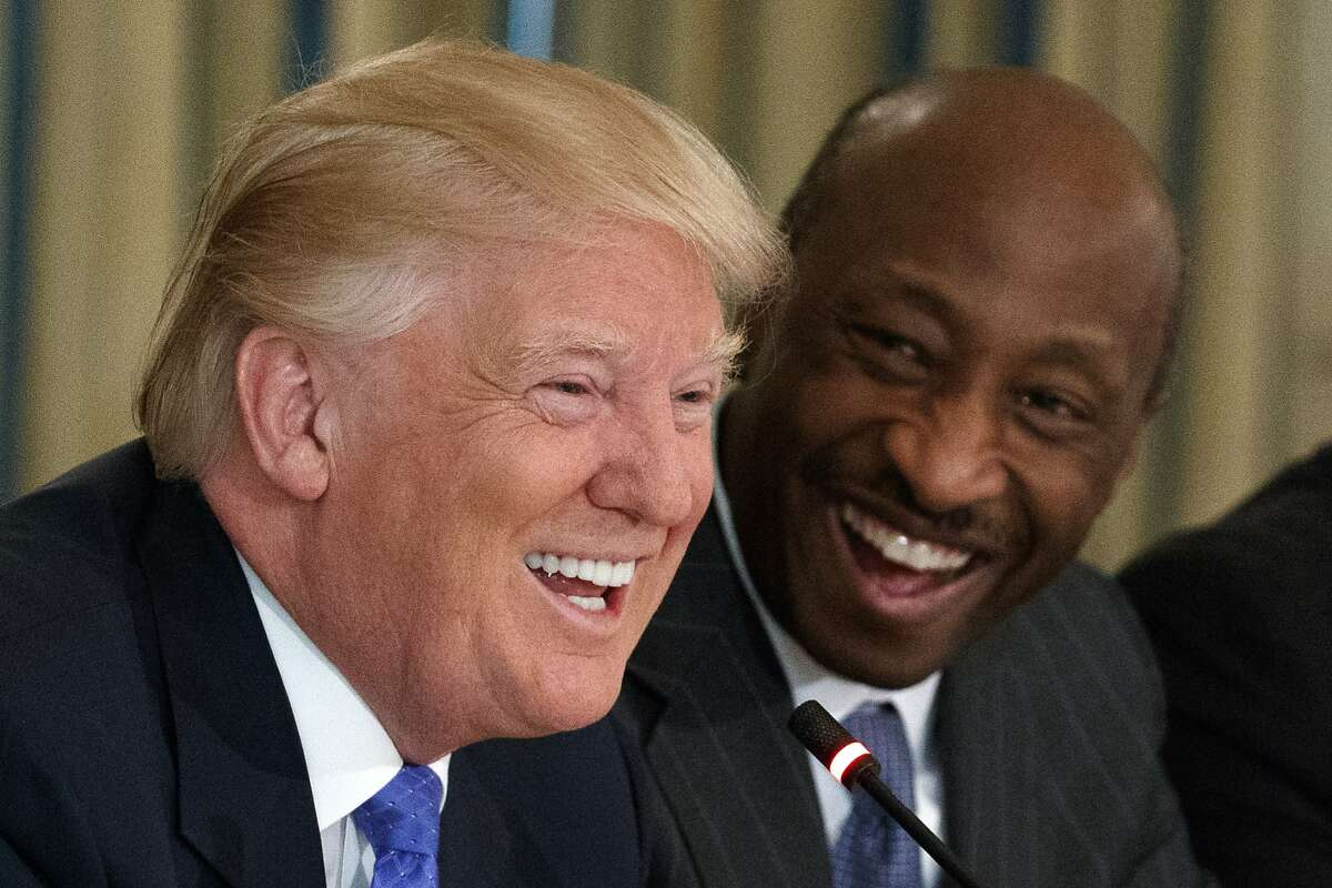 In this Feb. 23, 2017, file photo, Merck CEO Kenneth Frazier, right, watches as President Donald Trump speaks during a meeting with manufacturing executives at the White House in Washington. Fallout from President Donald Trump's reaction to violent, racial clashes in Virginia over the weekend continued in the business community. Frazier resigned from a federal panel created years ago to advise the U.S. president.