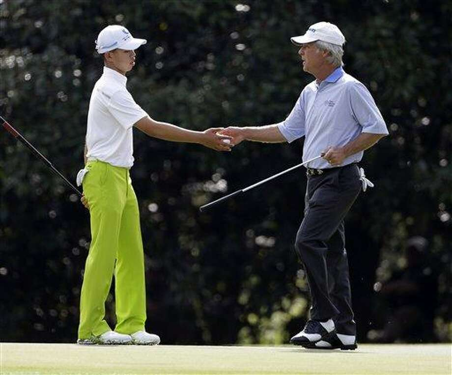 Ben Crenshaw, right, hands a golf ball to Amateur Tianlang Guan, of China, on the 11th hole during a practice round for the Masters golf tournament Monday, April 8, 2013, in Augusta, Ga. (AP Photo/Darron Cummings) Photo: AP / AP