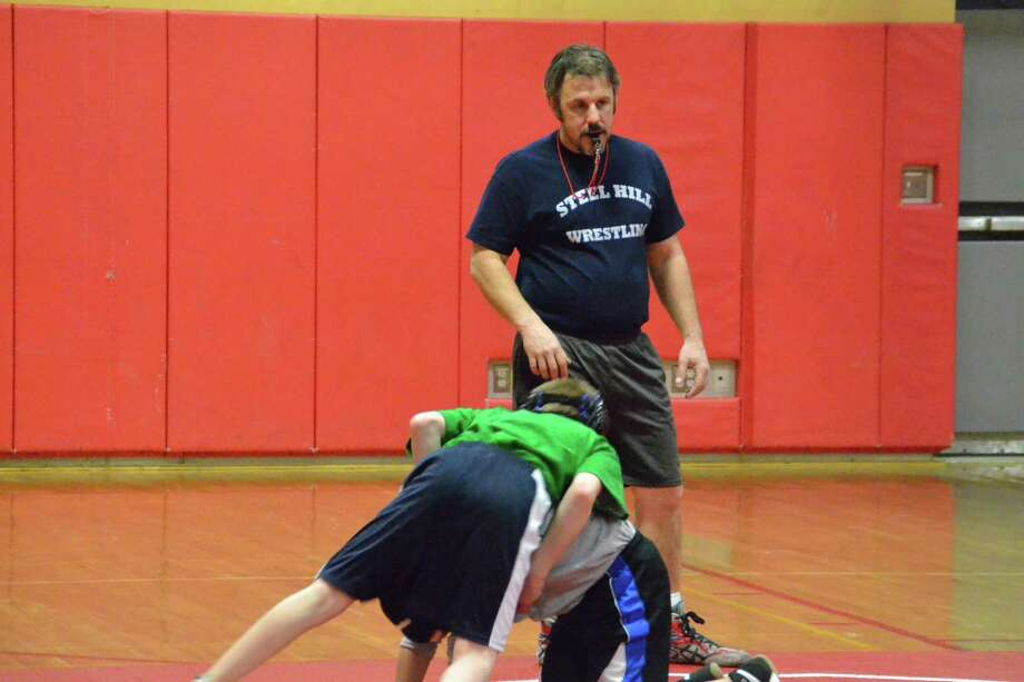 Steelhill wrestling program director Peter Folio coaching two of the wrestlers during practice. Pete Paguaga/Register Citizen