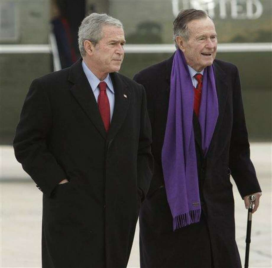 FILE - In this Dec. 26, 2008 file photo, President George W. Bush walks with his father, former President George H.W. Bush, at Andrews Air Force Base, Md. A criminal investigation is under way after a hacker apparently accessed private photos and emails sent between members of the Bush family, including both former presidents, according to reports Friday, Feb. 8, 2013. (AP Photo/Evan Vucci, File) Photo: AP / AP