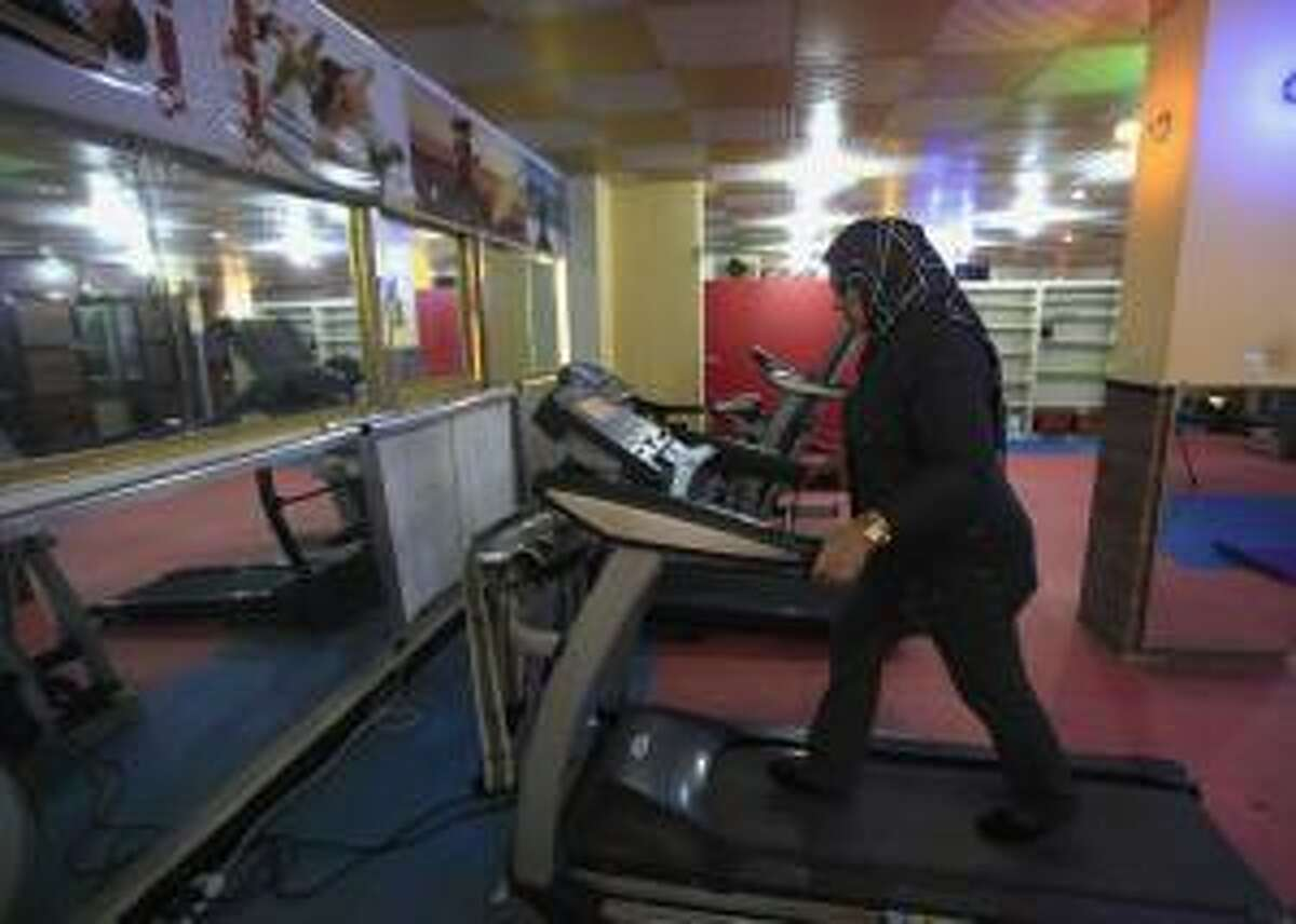 A woman works out on a treadmill at a gym in Baghdad December 2, 2012. Inssam, the owner of the gym, said she had noticed an increase in the number of women working out at the gym recently, a trend which she attributed to the influx of Western television programmes into the country after 2003. REUTERS/Thaier al-Sudani