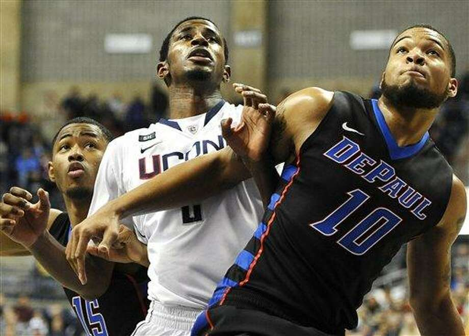 Connecticut's DeAndre Daniels, center looks for a rebound against DePaul's Moses Morgan, left, and DePaul's Derrell Robertson Jr., right, during the first half of an NCAA college basketball game in Storrs, Conn., Tuesday, Jan. 8, 2013. Connecticut won 99-78. (AP Photo/Jessica Hill) Photo: AP / FR125654 AP