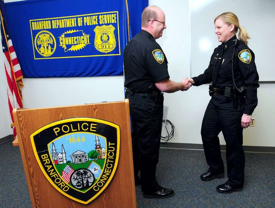 Branford Police Chief Kevin Halloran (center) congratulates Lt. Kris Hormuth (right) on her promotion during a ceremony at the Branford Police Department on 4/8/2013.Photo by Arnold Gold/New Haven Register  AG0491C