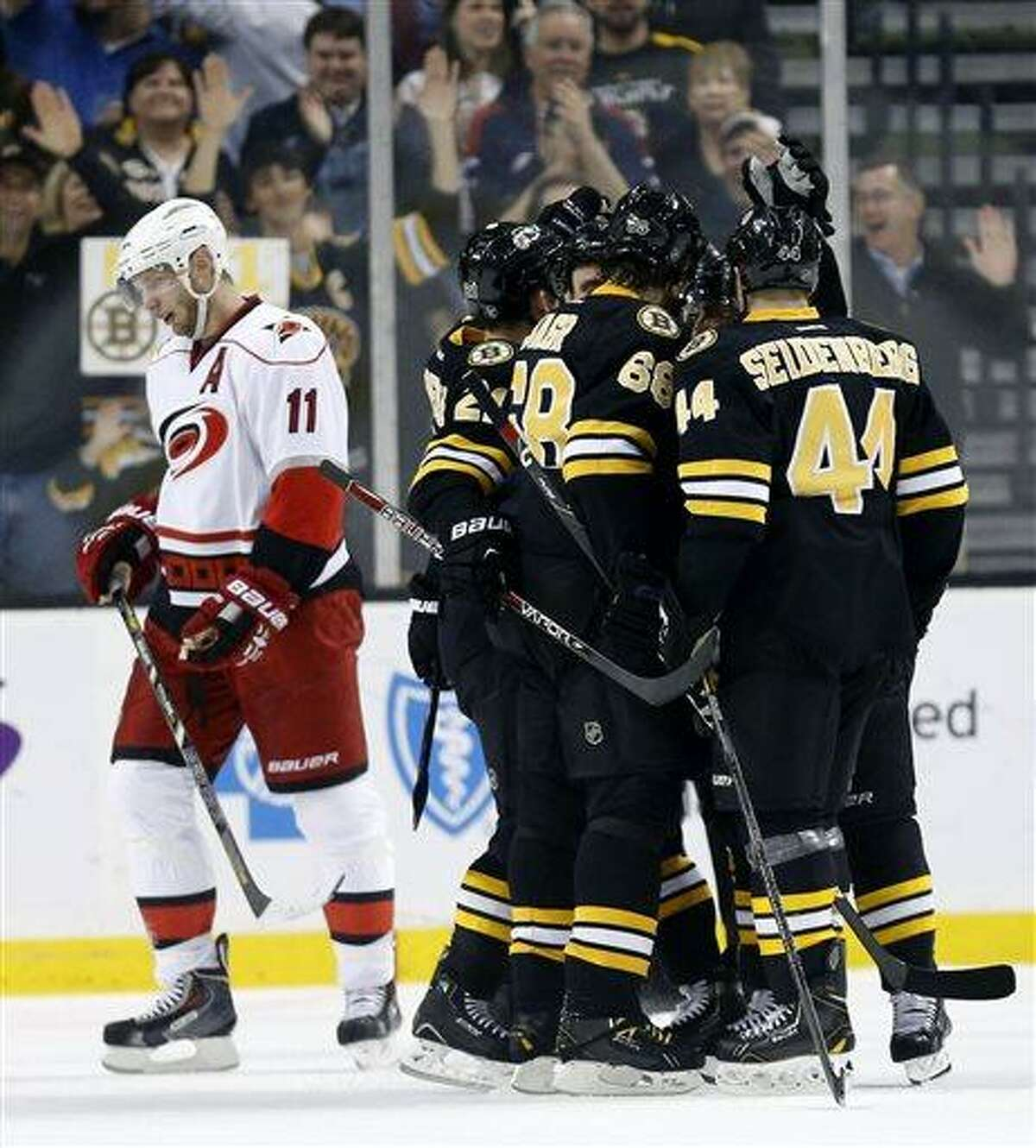 Boston Bruins' Dennis Seidenberg (44) and Jaromir Jagr (68) celebrate with teammates after Bruins' Brad Marchand scored his second goal as Carolina Hurricanes' Jordan Staal (11) skates away in the first period of an NHL hockey game in Boston, Monday, April, 8, 2013. (AP Photo/Michael Dwyer)