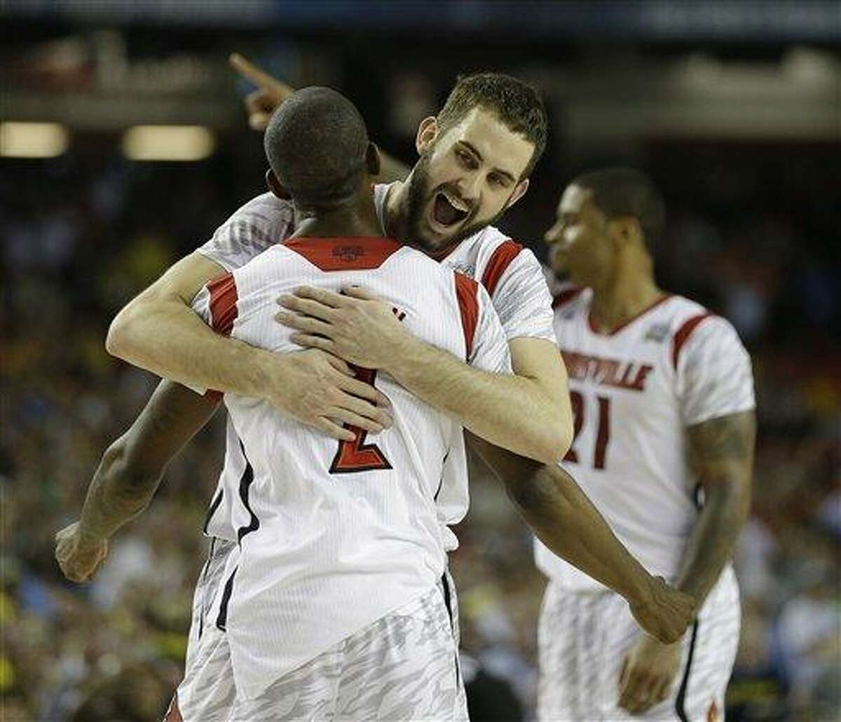 Louisville guard/forward Luke Hancock (11) embraces Louisville guard Russ Smith (2) after defeating Michigan after the second half of the NCAA Final Four tournament college basketball championship game Monday, April 8, 2013, in Atlanta. Louisville won 82-76. (AP Photo/David J. Phillip)