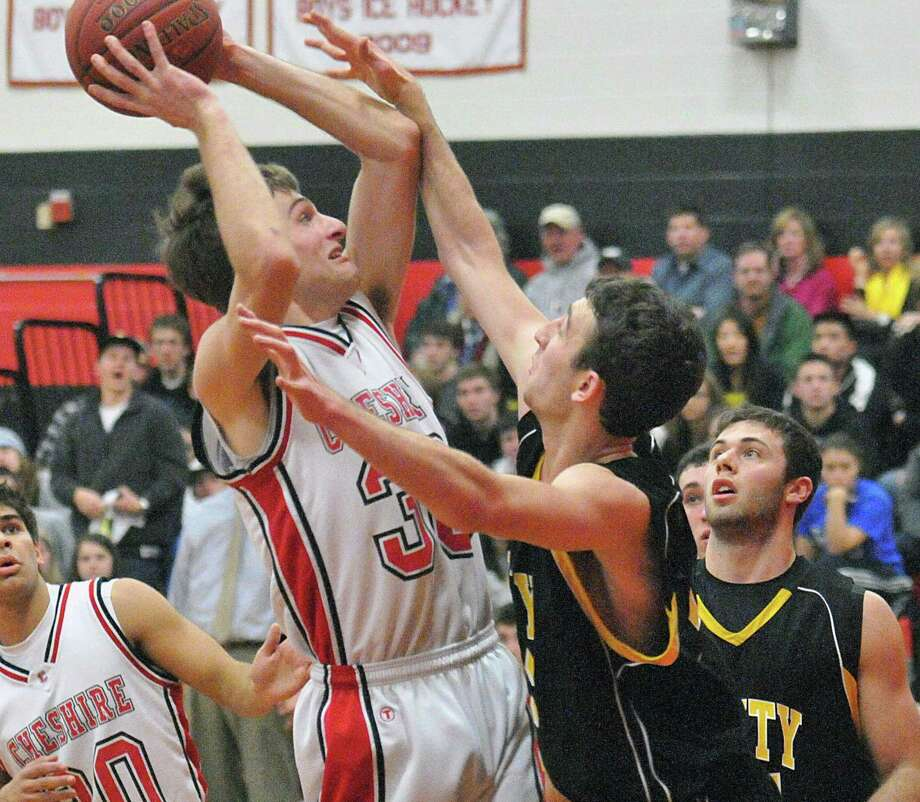 Cheshire's Tyler Post puts up a jumper as Amity's Matt Lettick defends during the first half of Cheshire's win last month. Amity clinched the SCC Housatonic Division on Thursday. Photo-Peter Casolino/Register.