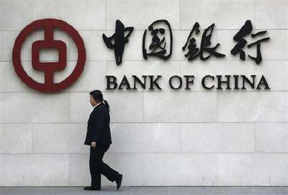A woman walks past a sign of Bank of China at its branch in Beijing March 26.