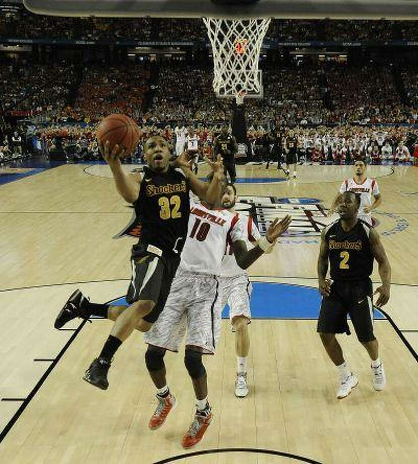 Wichita State's Tekele Cotton (32) heads to the hoop under the defense of Louisville's Gorgui Dieng (10) during the second half of the NCAA Final Four tournament college basketball semifinal game Saturday, April 6, 2013, in Atlanta Photo: AP / NCAA Photos