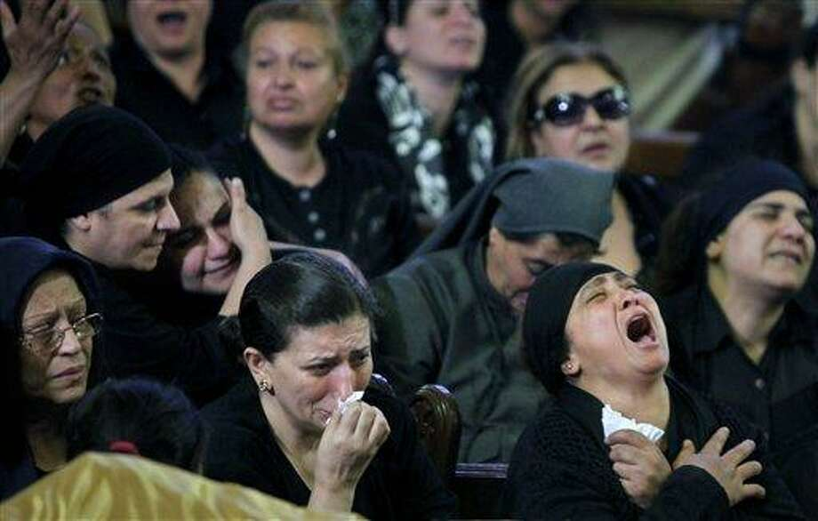 Egyptian Christians grieve during a funeral service at the Saint Mark Coptic cathedral in Cairo, Egypt, Sunday, April 7, 2013. Several Egyptians including 4 Christians and a Muslim were killed in sectarian clashes before dawn in Qalubiya, just outside of Cairo on Saturday, April 6, 2013. The Associated Press photo. Photo: AP / AP