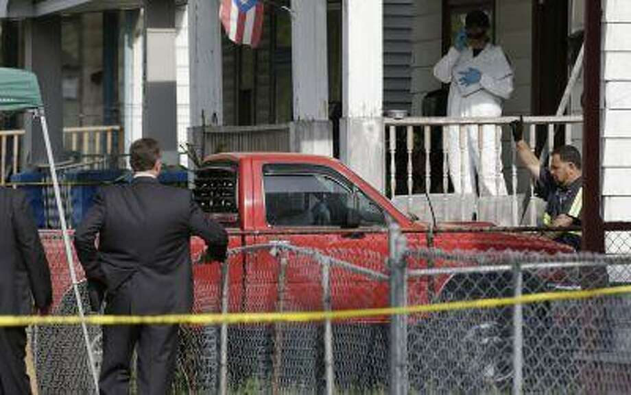 A truck is pulled out a driveway from a house Tuesday, May 7, 2013, where three women who vanished a decade ago were held, in Cleveland. The women were found safe Monday, and police arrested three brothers accused of holding the victims against their will. (AP Photo/Tony Dejak) Photo: AP / AP