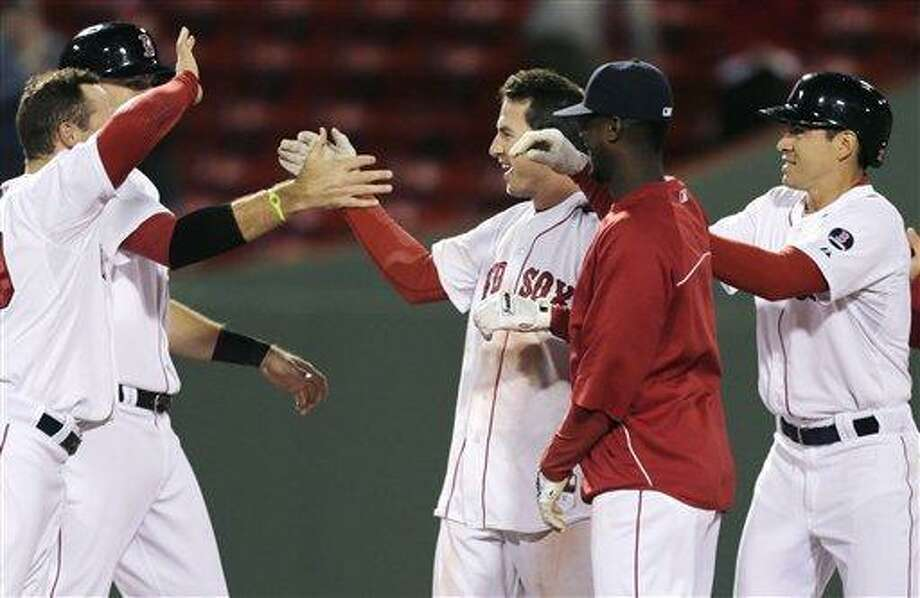 Boston Red Sox shortstop Stephen Drew is congratulated by teammates after his game-winning, RBI double in the eleventh inning of a baseball game against the Minnesota Twins at Fenway Park in Boston, Monday, May 6, 2013.  The Red Sox won 6-5. (AP Photo/Charles Krupa) Photo: AP / AP