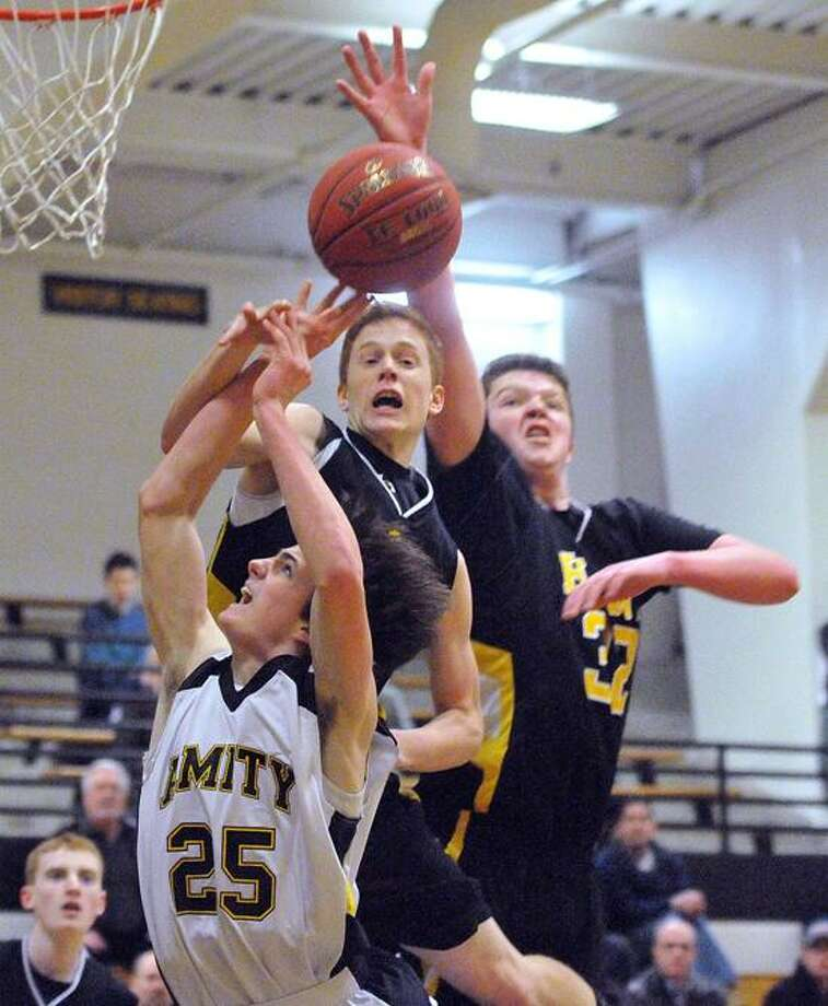 Amity's Dave Ryan takes the foul as Hand's Sam Jablonski, left, and Phil Crampton defend during the first period. Peter Casolino/Register