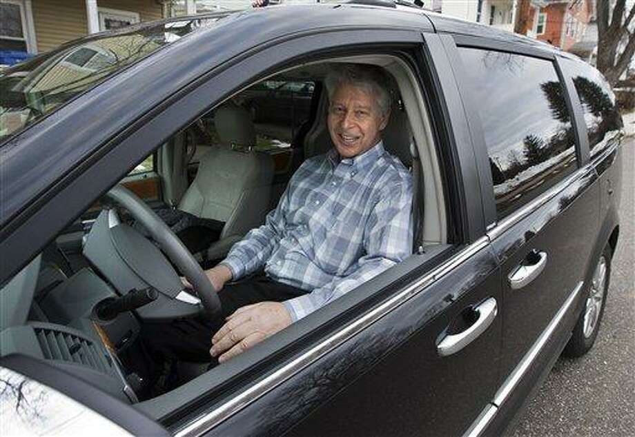 In this March 1, 2013 photo, Jim Casso sits in the black van that he uses for his job in front of his Meriden, Conn., home.  Casso's unique job is picking up the deceased whose bodies are being donated to science for Quinnipiac University's new medical school. Casso takes the bodies to the lab and embalms them for students training in their medical education. (AP Photo/Record-Journal, Christopher Zajac) Photo: AP / Record-Journal