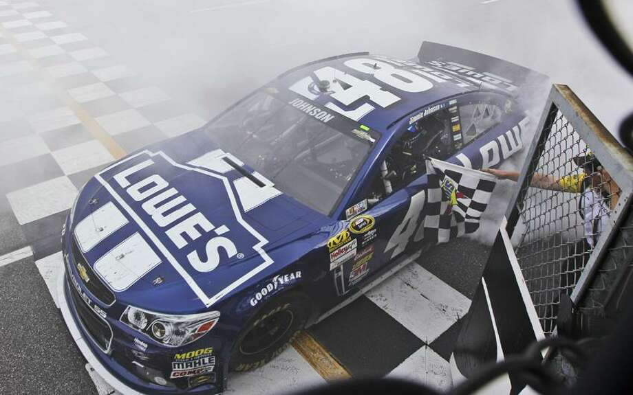 Jimmie Johnson grabs the checkered flag as he celebrates winning the STP 500 Sprint Cup  series auto race at Martinsville Speedway in Martinsville, Va., Sunday April 7, 2013.  (AP Photo/Steve Helber) Photo: AP / AP2013