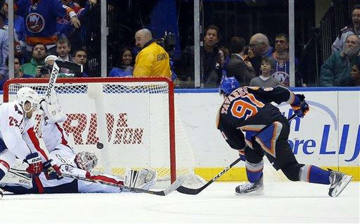 The New York Islanders John Tavares (91) shoots the puck past Washington Capitals goalie Philipp Grubauer (31) for his first goal of the third period of an NHL hockey game at the Nassau Coliseum in Uniondale, N.Y., Saturday, March 9, 2013. The Islanders won 5-2.(AP Photo/Paul J. Bereswill)