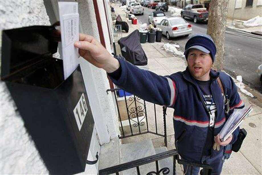 FILE - In this Tuesday, March 2, 2010 file photo, letter carrier Kevin Pownall delivers mail in Philadelphia. The financially struggling U.S. Postal Service announced on Wednesday, Feb. 6, 2013 it will stop delivering mail on Saturdays but continue to deliver packages six days a week under a plan aimed at saving about $2 billion a year.  (AP Photo/Matt Rourke, File) Photo: AP / AP