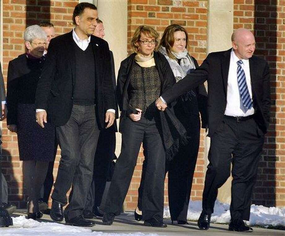 Former U.S. Rep. Gabrielle Giffords, center, holds hands with her husband, Mark Kelly, while exiting Town Hall at Fairfield Hills Campus in Newtown, Conn. after meeting with Newtown First Selectman Pat Llodra and other officials on Friday, Jan. 4, 2013. At far left is Lt. Gov. Nancy Wyman; behind Giffords to the left is U.S. Sen. Richard Blumenthal. Giffords also met with families of the victims of the Sandy Hook Elementary massacre that left 26 people dead. (AP Photo/The News-Times, Jason Rearick) Photo: AP / News-Times