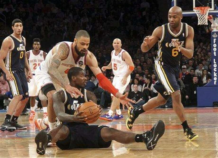 New York Knicks' Tyson Chandler, left, fights for a loose ball against Utah Jazz's Marvin Williams during the second half of an NBA basketball game on Saturday, March 9, 2013, at Madison Square Garden in New York. The Knicks won 113-84. (AP Photo/Mary Altaffer) Photo: AP / AP