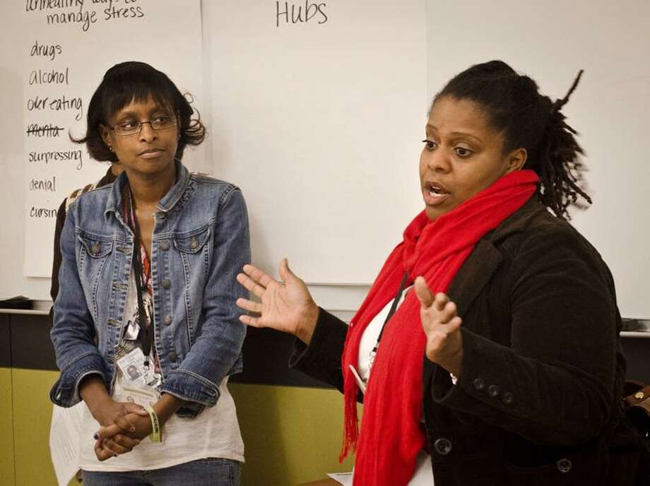 Kia Levy, right, program manager of the New Haven Moms Partnership, talks about the ways moms can come together to support each other and deal with stress. The organization was conducting a workshop at Gateway Community College. Looking on is Kim Streater, also of the partnership.  Melanie Stengel/Register